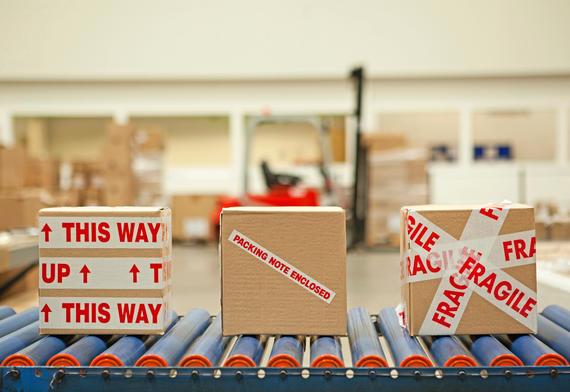 Three cardboard boxes with parcel printed tape on conveyor belt